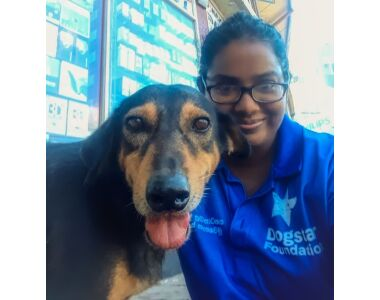 Dogstar dog Fred and team member Anjali sitting next to each other looking at the camera
