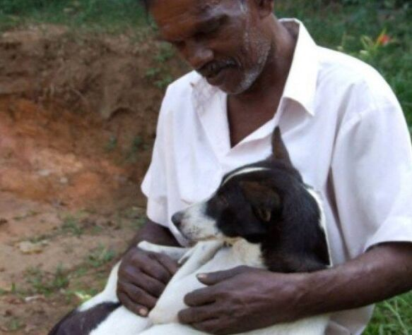 sri lankan street dog owner cuddles his dog before surgery