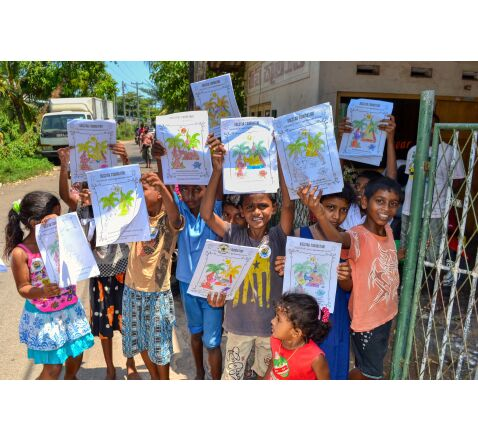 Children holding up completed dogstar colouring books