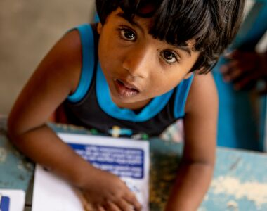 A child looks at the camera whilst working on their Dogstar education booklet.